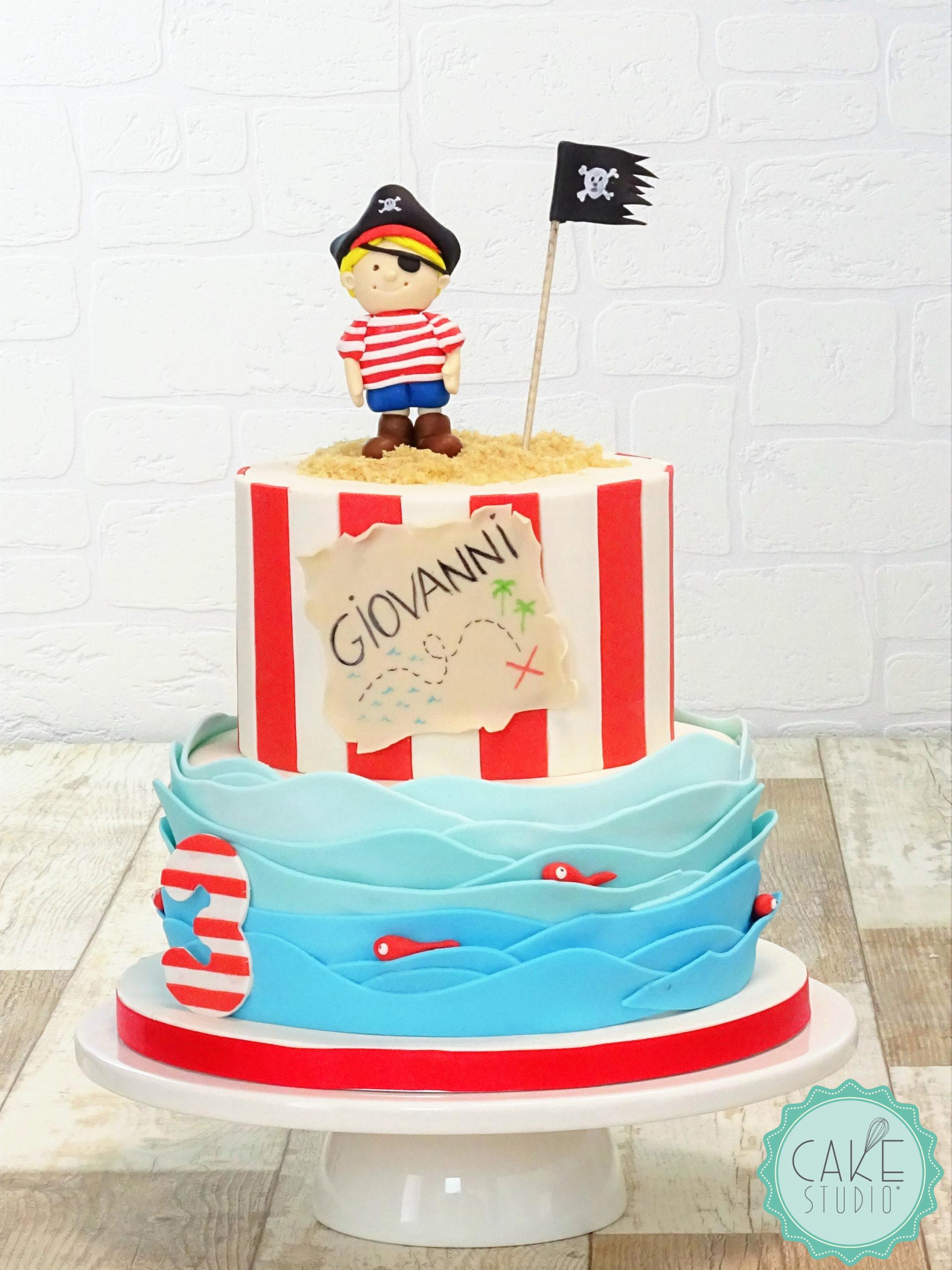 torta con onde azzurre, righe bianche e rosse e pirata con bandiera nera e teschio