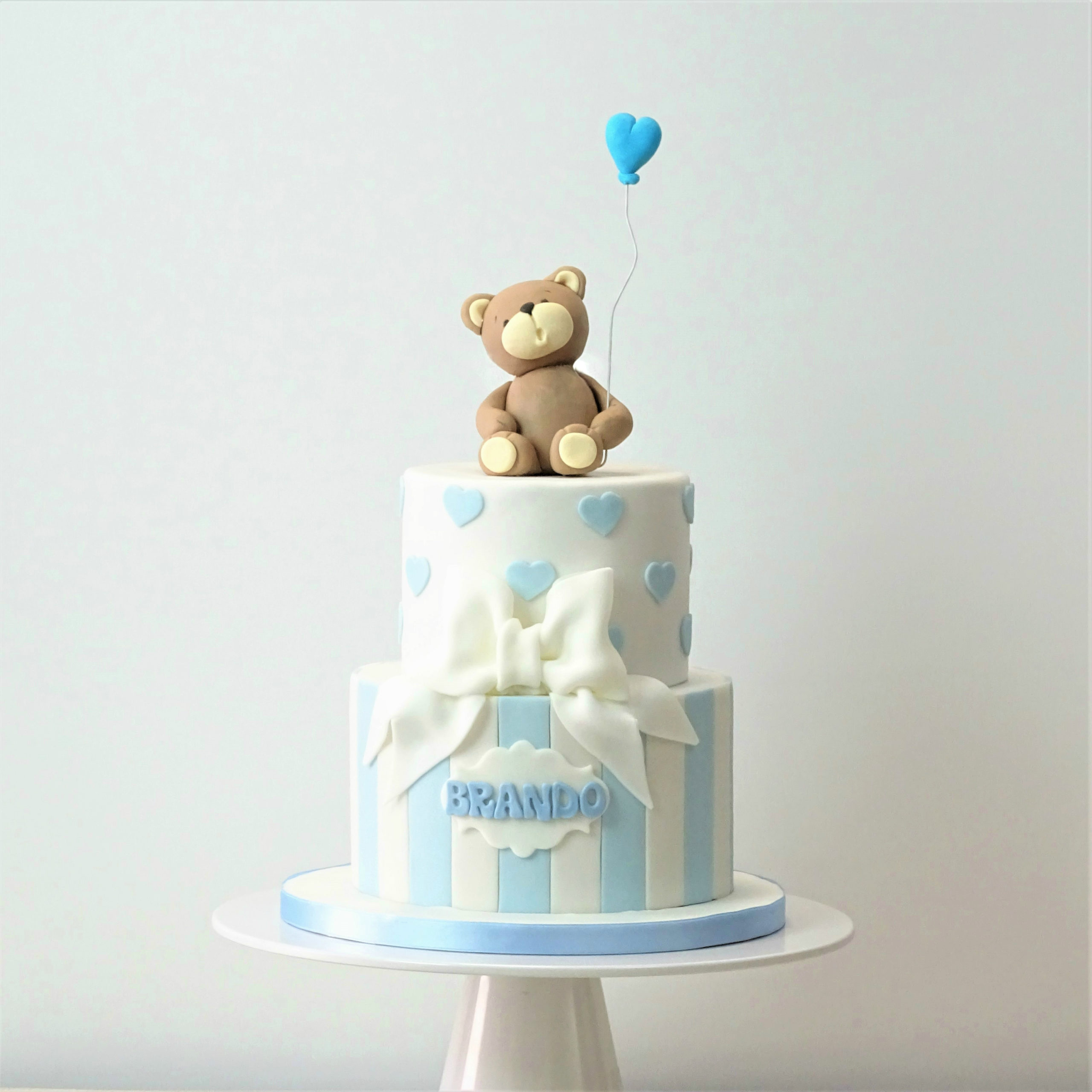 torta con righe bianche e azuure, fiocco e cuoricini, con orsetto con palloncino