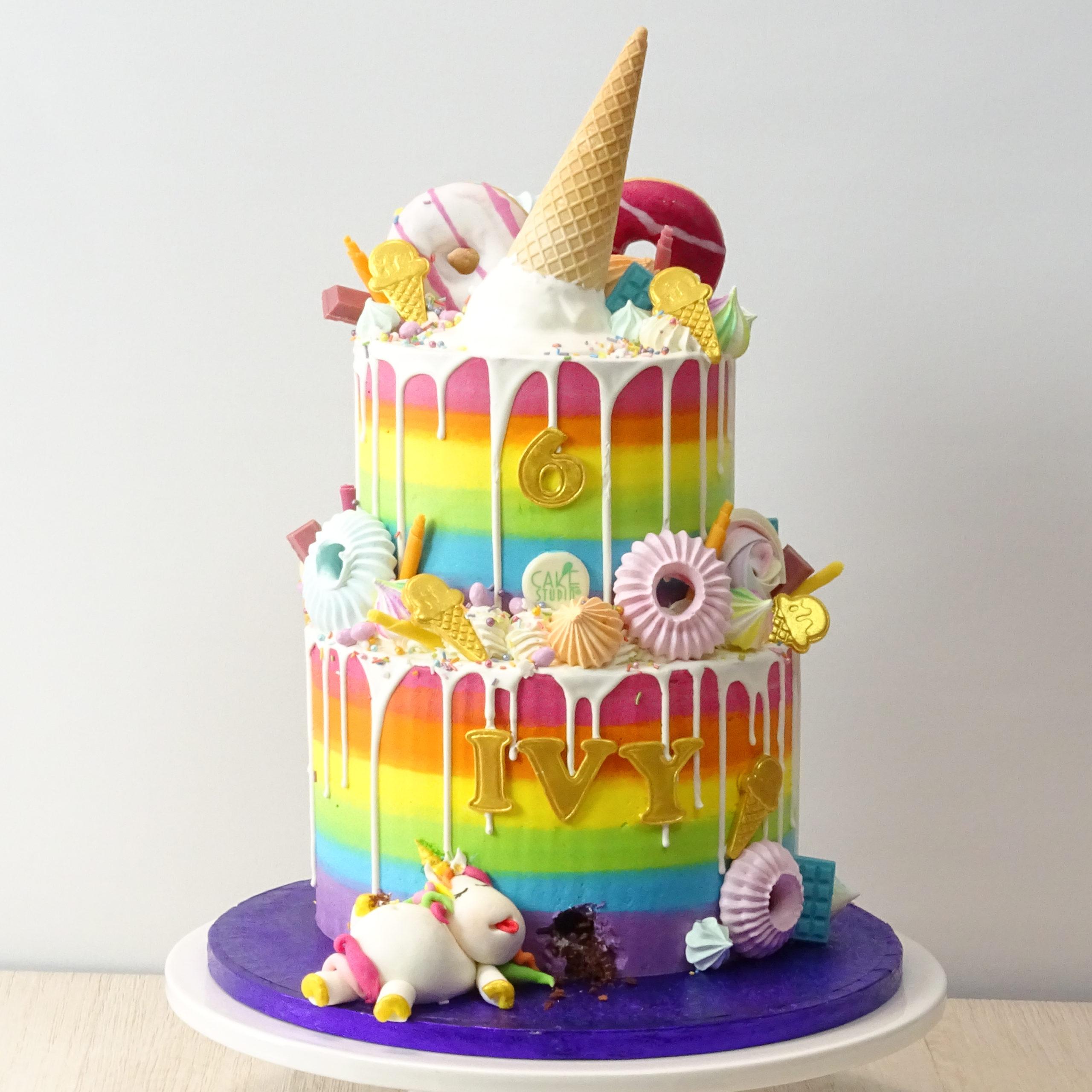 drip cake arcobaleno con unicorno e gelato colato