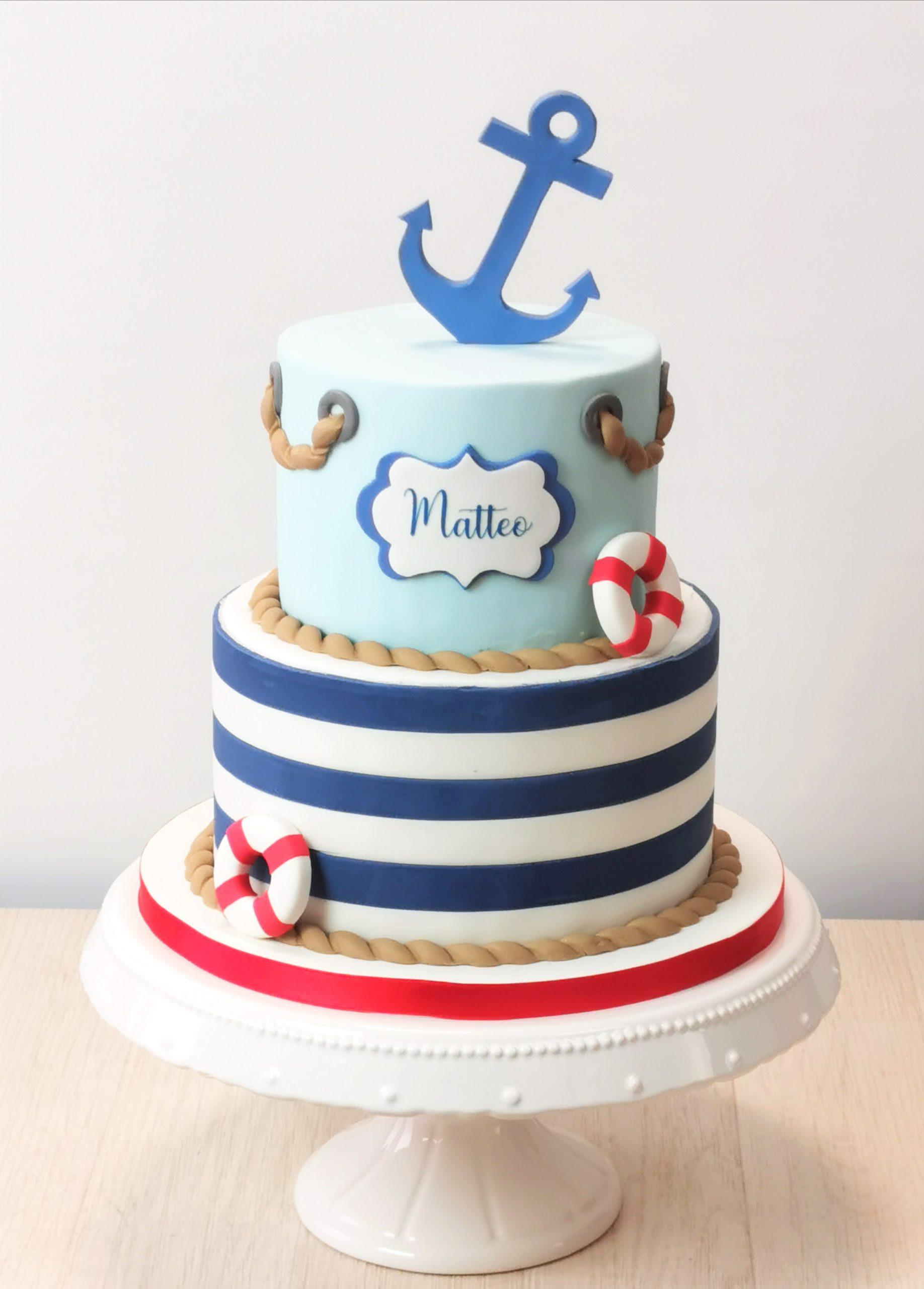 torta stile marinaro a righe bianche e blu con corda ancora e salvagente