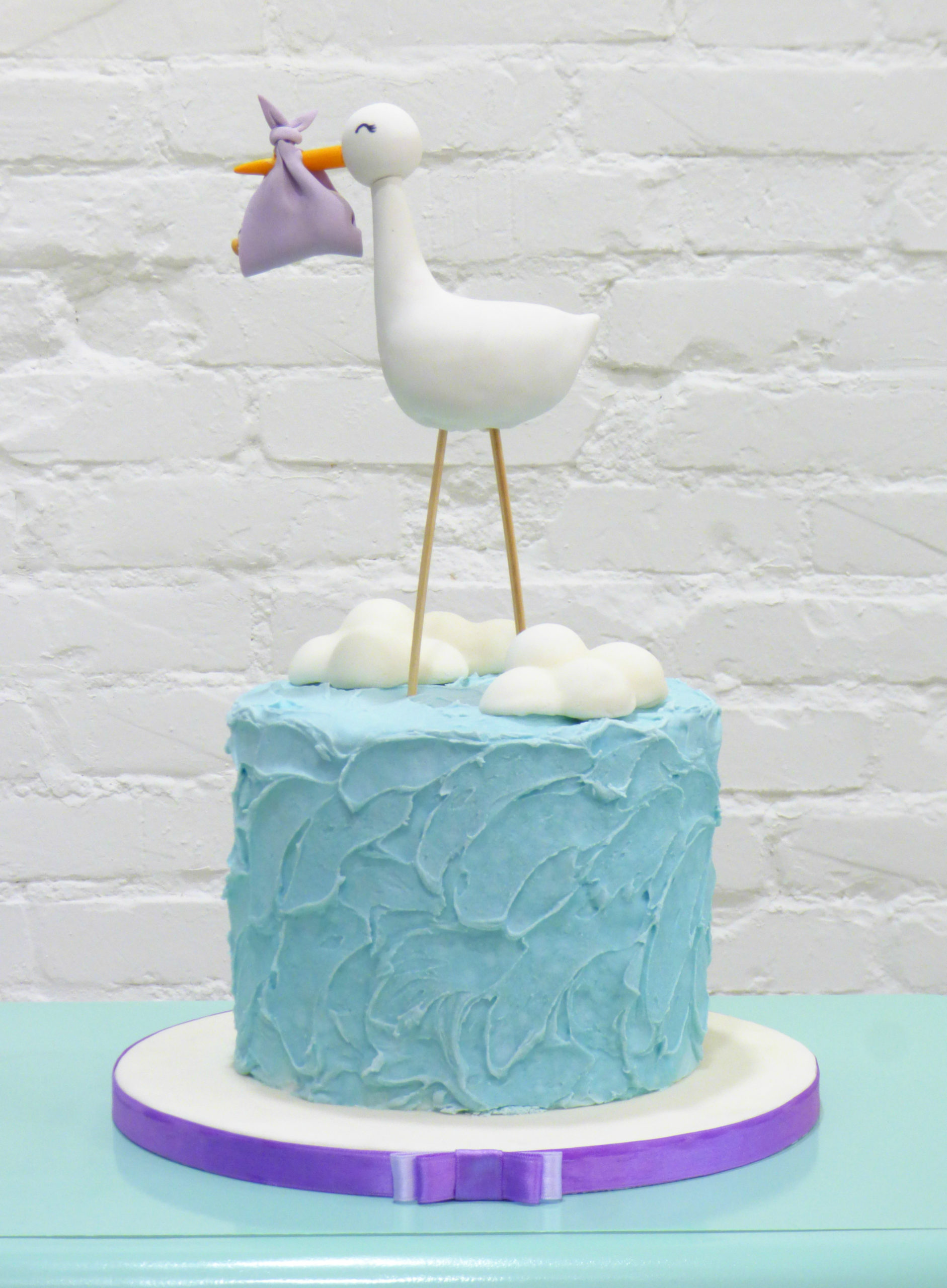 torta azzurra con cicogna fagotto neonato e nuvole
